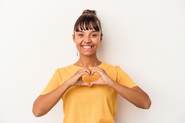 Młoda kobieta rasy mieszanej na białym tle uśmiechnięta i pokazująca kształt serca rękami.
