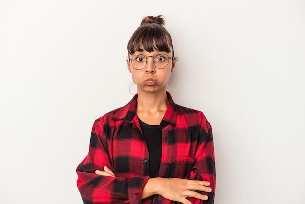Młoda kobieta rasy mieszanej na białym tle wieje w policzki, ma zmęczony wyraz twarzy. koncepcja wyraz twarzy.