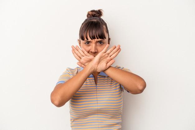 Młoda kobieta rasy mieszanej na białym tle wykonująca gest odmowy
