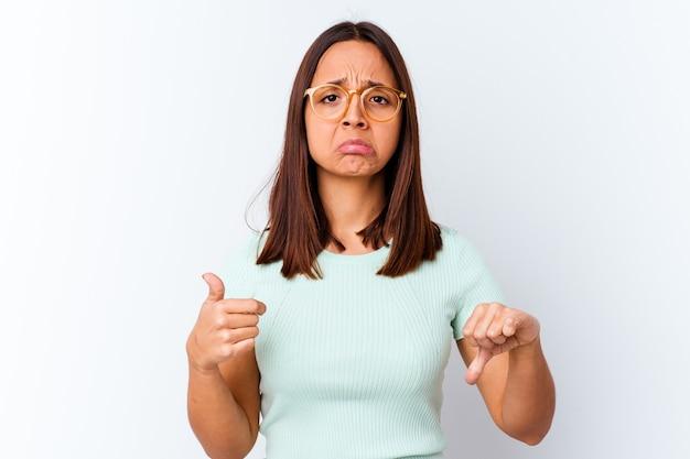 Młoda kobieta rasy mieszanej na białym tle wyświetlono kciuk w górę i w dół, trudna koncepcja wyboru