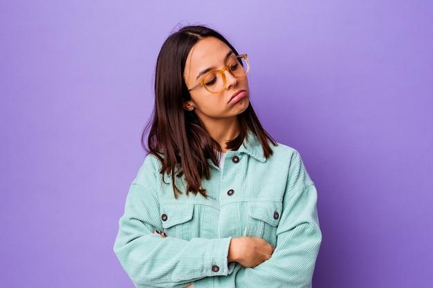 Młoda kobieta rasy mieszanej na białym tle zmęczona powtarzalnym zadaniem.