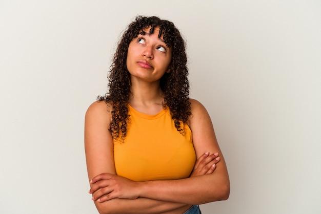 Młoda kobieta rasy mieszanej na białym tle zmęczony powtarzającym się zadaniem.