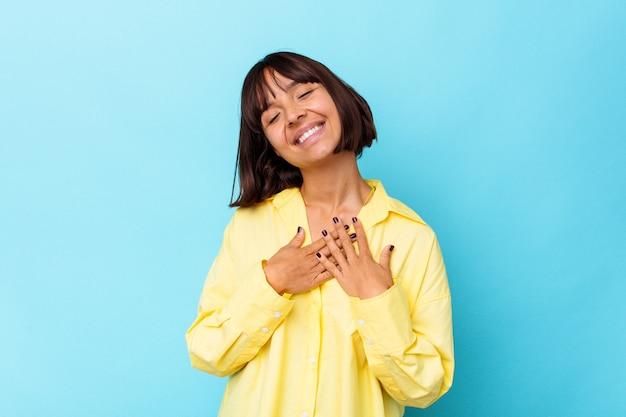 Młoda kobieta rasy mieszanej na niebieskim tle ma przyjazny wyraz twarzy, przyciskając dłoń do klatki piersiowej. koncepcja miłości.