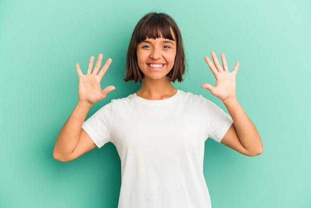 Młoda kobieta rasy mieszanej na niebieskim tle pokazano numer dziesięć rękami.