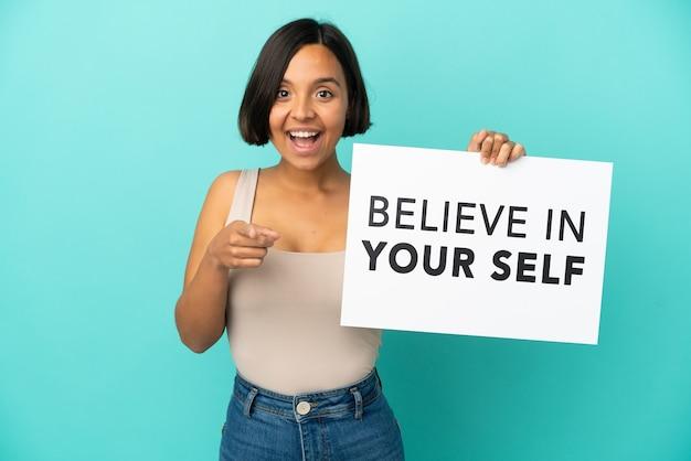 Młoda kobieta rasy mieszanej na niebieskim tle trzymająca deskę we want you i wskazująca na przód