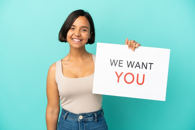 Młoda kobieta rasy mieszanej na niebieskim tle trzymająca deskę we want you ze szczęśliwym wyrazem twarzy