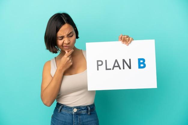 Młoda kobieta rasy mieszanej na niebieskim tle trzymająca tabliczkę z napisem plan b i myśląca and