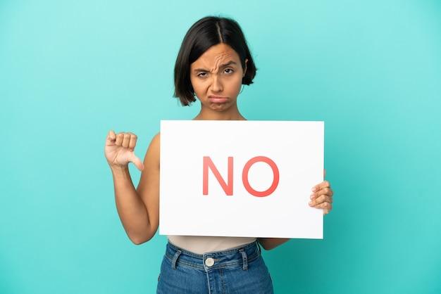 Młoda kobieta rasy mieszanej na niebieskim tle trzymająca tabliczkę z tekstem nie i robiąca zły sygnał