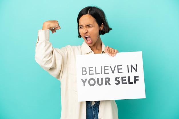 """Młoda kobieta rasy mieszanej na niebieskim tle trzymająca tabliczkę z tekstem """"uwierz w siebie"""" i wykonująca silny gest"""
