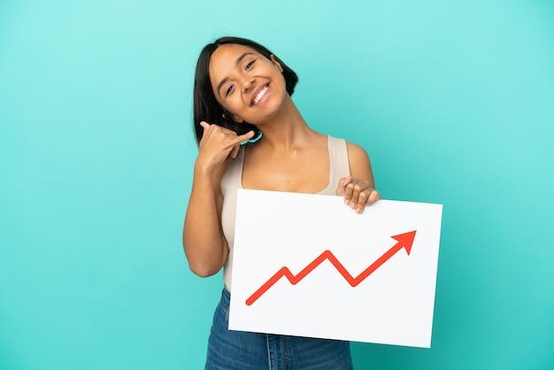 Młoda kobieta rasy mieszanej na niebieskim tle trzymająca znak z rosnącym symbolem strzałki statystyk i wykonująca gest telefoniczny