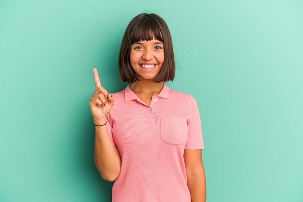 Młoda kobieta rasy mieszanej na niebiesko pokazano numer jeden palcem.