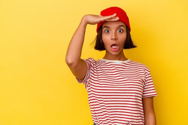 Młoda kobieta rasy mieszanej na żółtym tle krzyczy głośno, ma otwarte oczy i napięte ręce.