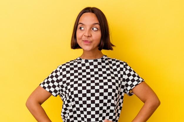 Młoda kobieta rasy mieszanej na żółtym tle marząc o osiągnięciu celów i celów