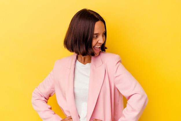 Młoda kobieta rasy mieszanej na żółtym tle śmieje się i zamyka oczy, czuje się zrelaksowana i szczęśliwa.