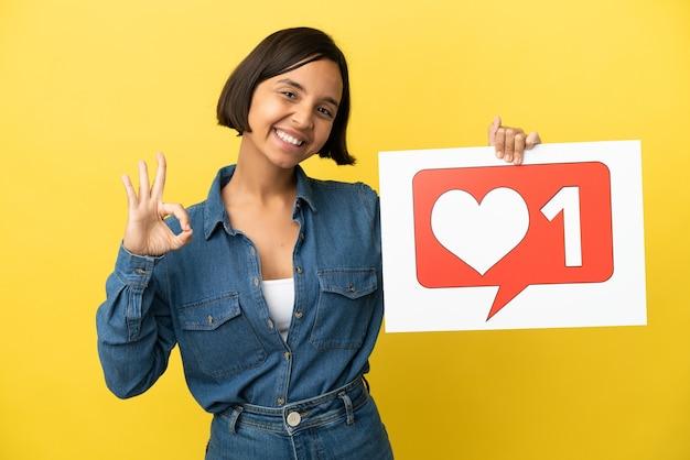 Młoda kobieta rasy mieszanej na żółtym tle trzymająca tabliczkę z ikoną like i świętującą zwycięstwo