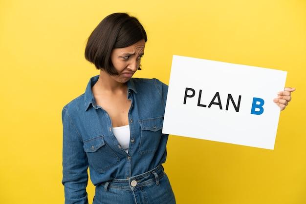 Młoda kobieta rasy mieszanej na żółtym tle trzymająca tabliczkę z komunikatem plan b ze smutnym wyrazem twarzy