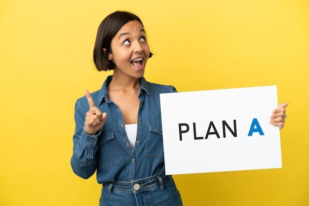 Młoda kobieta rasy mieszanej na żółtym tle trzymająca tabliczkę z napisem plan a i myśląca