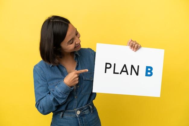 Młoda kobieta rasy mieszanej na żółtym tle trzymająca tabliczkę z napisem plan b