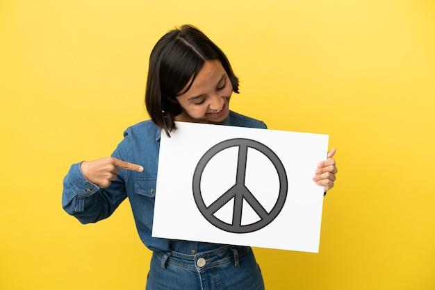 Młoda kobieta rasy mieszanej na żółtym tle trzymająca tabliczkę z symbolem pokoju i wskazującą go
