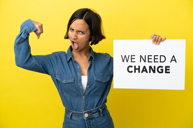 Młoda kobieta rasy mieszanej na żółtym tle trzymająca tabliczkę z tekstem potrzebujemy zmiany i wykonująca silny gest