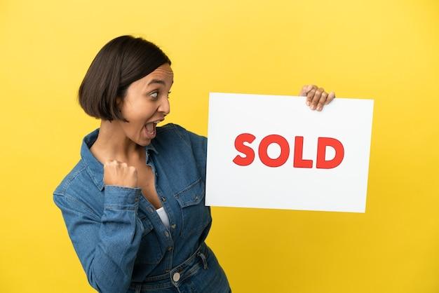 Młoda kobieta rasy mieszanej na żółtym tle trzymająca tabliczkę z tekstem sprzedano i świętująca zwycięstwo