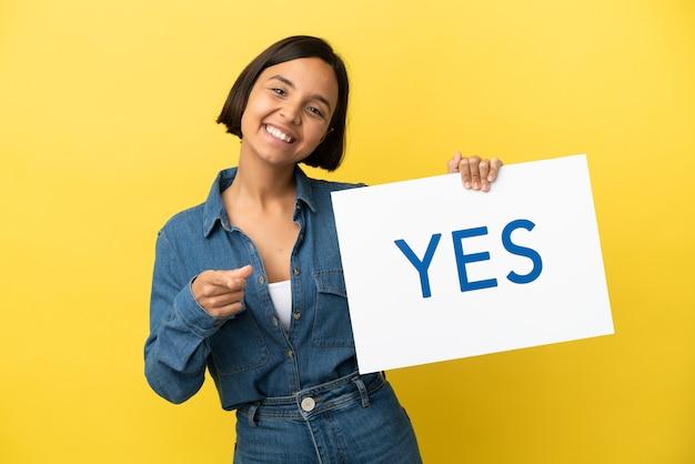 Młoda kobieta rasy mieszanej na żółtym tle trzymająca tabliczkę z tekstem tak i wskazującą going