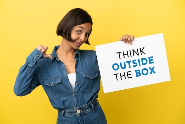 Młoda kobieta rasy mieszanej na żółtym tle trzymająca tabliczkę z tekstem think outside the box z dumnym gestem