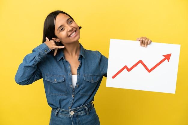 Młoda kobieta rasy mieszanej na żółtym tle trzymająca znak z rosnącym symbolem strzałki statystyk i wykonująca gest telefoniczny
