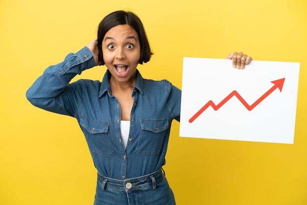 Młoda kobieta rasy mieszanej na żółtym tle trzymająca znak z rosnącym symbolem strzałki statystyki z zaskoczonym wyrazem twarzy