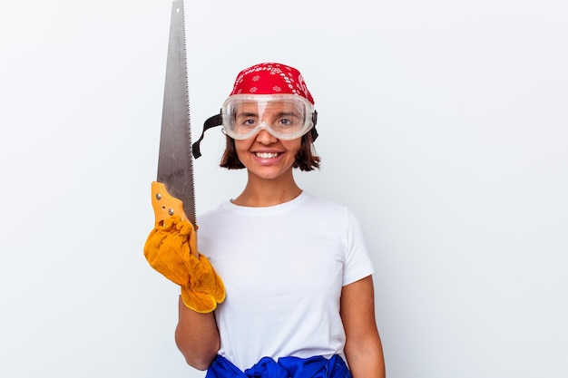 Młoda kobieta rasy mieszanej naprawy jej domu z piłą na białym tle na białej ścianie