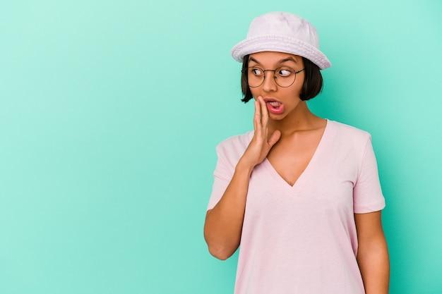 Młoda kobieta rasy mieszanej, odizolowana na niebieskiej ścianie, mówi tajną wiadomość o gorącym hamowaniu i patrzy na bok