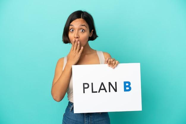Młoda kobieta rasy mieszanej odizolowana na niebieskim tle trzymająca tabliczkę z komunikatem plan b ze zdziwionym wyrazem twarzy