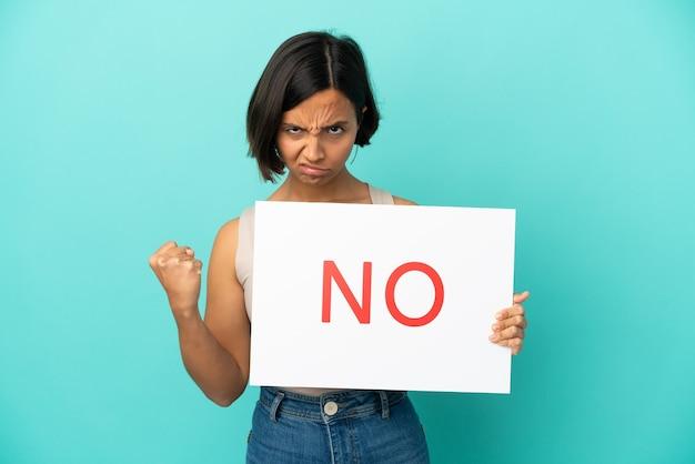Młoda kobieta rasy mieszanej odizolowana na niebieskim tle trzymająca tabliczkę z tekstem nie i zła