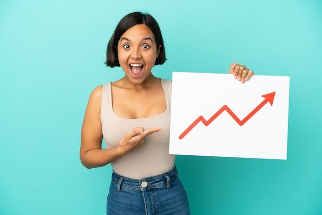 Młoda kobieta rasy mieszanej odizolowana na niebieskim tle trzymająca znak z rosnącym symbolem strzałki statystyki z zaskoczonym wyrazem twarzy