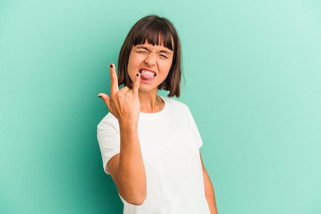 Młoda kobieta rasy mieszanej odizolowana na niebiesko pokazując rockowy gest palcami