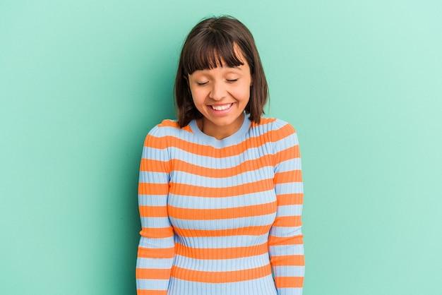 Młoda kobieta rasy mieszanej odizolowana na niebiesko śmieje się i zamyka oczy, czuje się zrelaksowana i szczęśliwa.
