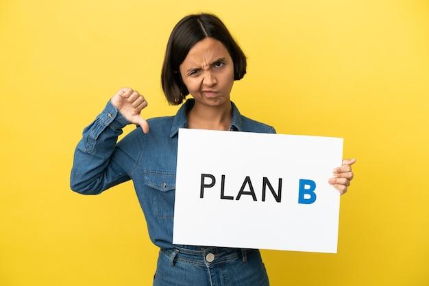 Młoda kobieta rasy mieszanej odizolowana trzymająca plakat z komunikatem plan b i robiąca zły sygnał