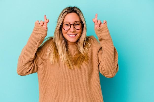 Młoda kobieta rasy mieszanej odizolowane na niebiesko skrzyżowane palce za szczęście