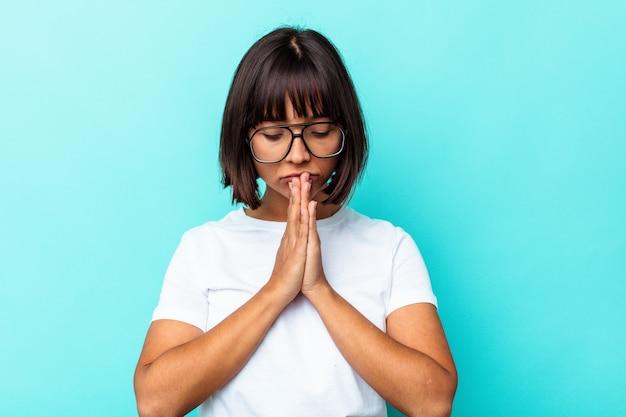 Młoda kobieta rasy mieszanej odosobniona na niebieskim tle modląca się, okazująca oddanie, osoba religijna szukająca boskiej inspiracji.