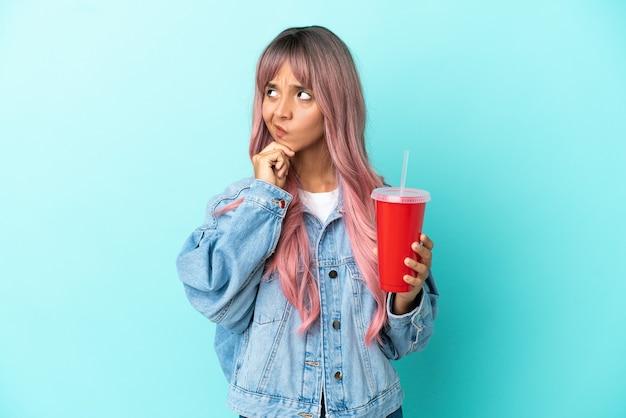 Młoda kobieta rasy mieszanej pijąca świeży napój na białym tle na niebieskim tle, mająca wątpliwości i myśląca