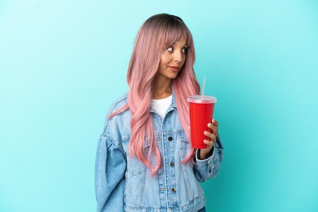 Młoda kobieta rasy mieszanej pijąca świeży napój na białym tle na niebieskim tle, patrząc w bok