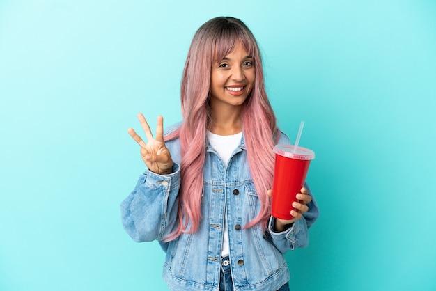 Młoda kobieta rasy mieszanej pijąca świeży napój na białym tle na niebieskim tle szczęśliwa i licząca trzy palcami