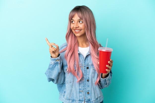 Młoda kobieta rasy mieszanej pijąca świeży napój na białym tle na niebieskim tle, wskazując na świetny pomysł