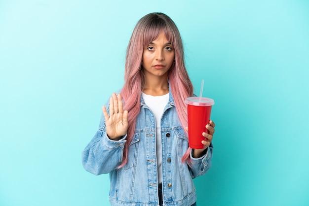 Młoda kobieta rasy mieszanej pijąca świeży napój na białym tle na niebieskim tle, wykonując gest zatrzymania