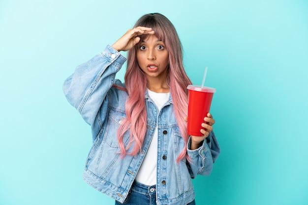Młoda kobieta rasy mieszanej pijąca świeży napój na białym tle na niebieskim tle, wykonująca gest zaskoczenia, patrząc w bok