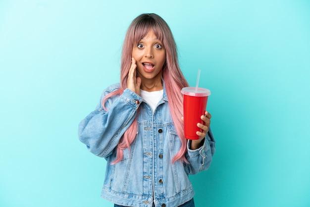 Młoda kobieta rasy mieszanej pijąca świeży napój na białym tle na niebieskim tle z zaskoczeniem i zszokowanym wyrazem twarzy