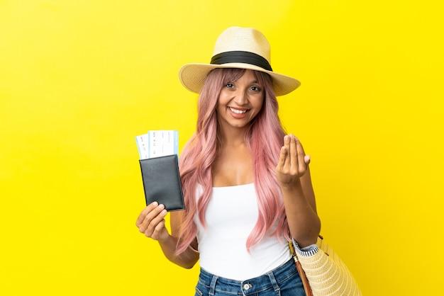 Młoda kobieta rasy mieszanej posiadania paszportu i torbę plażową na białym tle na żółtym tle zapraszając przyjść z ręką. cieszę się, że przyszedłeś