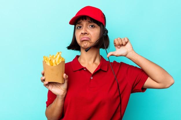 Młoda kobieta rasy mieszanej pracownik restauracji fast food trzymający frytki na białym tle na niebieskim tle czuje się dumny i pewny siebie, przykład do naśladowania.