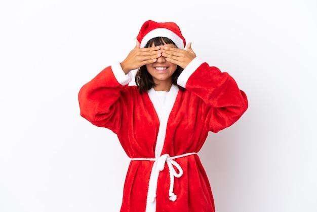 Młoda kobieta rasy mieszanej przebrana za świętego mikołaja na białym tle zakrywająca oczy rękami