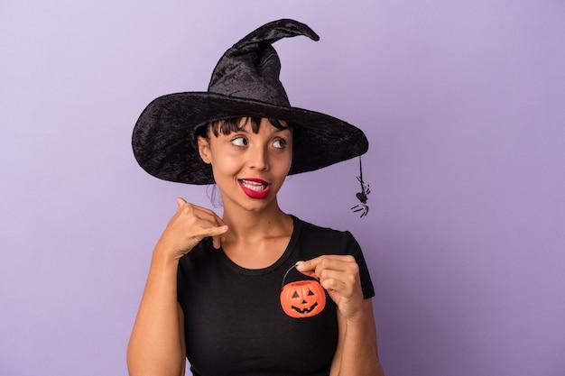 Młoda kobieta rasy mieszanej przebrana za wiedźmę na białym tle na fioletowym tle pokazujący gest połączenia z telefonem komórkowym palcami.